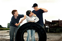 Three boys posing with a big tyre.