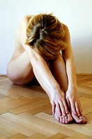 a naked woman sitting on the floor with her head resting on her knee.