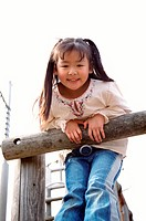 Young Girl Leaning Against a Wooden Post on a Climbing Frame