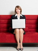 Businesswoman Sitting on a Sofa With a Laptop