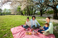 Family Sitting in a Park Enjoying a Picnic