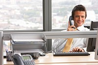 Businessman at desk in office, using computer and telephone, smiling