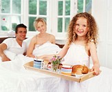 Girl (4-6) bringing parents breakfast in bed, smiling, portrait