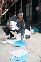 Businessman outdoors, picking up spilt papers from pavement