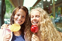 Two Teenage Girls Laugh and Smile With a Toffee Apple and a Lollipop