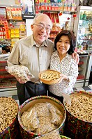 Senior couple in Chinese-herb store, smiling, portrait