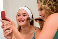 Mother helping daughter (13-15) with make-up, smiling