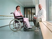Mature male doctor by female patient in wheelchair, smiling, portrait