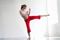 Woman practicing martial arts kick