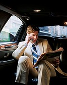 Young businessman reading newspaper in back of car, using mobile phone