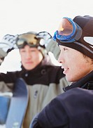 Man wearing ski goggles around head, smiling, man in background