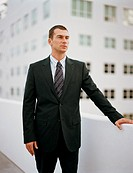 Businessman outdoors, resting hand on wall, looking away