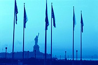 Statue of Liberty and the american flags with a bluish sky