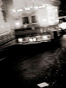 An ambulance is captured at night with a 2 second time exposure to create a ghostly, haunting feeling. The image is in black and white, with a slight ...
