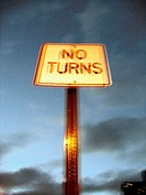 Blurred Street sign 'No Turns' shot against a dusk sky gives a surreal effect that seems to emanate a cosmic energy