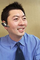 Asian male with cell phone remote ear/microphone bluetooth piece