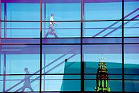 People crossing glass bridge in Nordea Bank building. Spire of Nikolaj Kirke in background, Copenhagen, Denmark