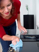 Woman dusting stereo