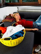 Woman sleeping by laundry basket