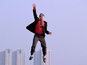 Young Asian (Chinese) businessman caught in mid-air falling, ground not visible, hi-rise buildings in the background