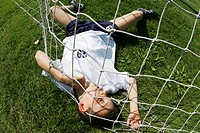 Young boy lying in a goalnet