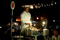 Jemaa El Fna place - Shopkeeper selling escargots on a stand at night