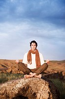 Man Seated on Rock in Meditative Pose