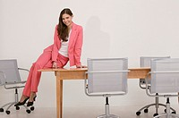 Businesswoman sitting on desk, portrait.