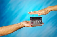 Close-up of a man holding a calculator with a woman's hand above it