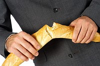 Mid section view of a businessman breaking a loaf of bread