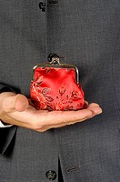 Mid section view of a businessman holding a change purse