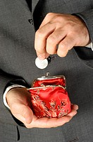Mid section view of a businessman putting money into a change purse