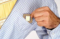 Mid section view of a businessman putting a computer chip into his shirt pocket
