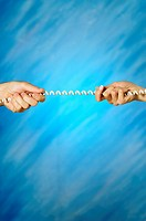Close-up of a man and a woman's hands pulling a telephone cord