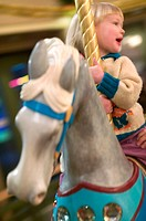 3 year old Caucasian girl on carousel horse