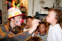 Clown doing face painting on birthday party