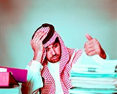 Overworked Arab businessman with piles of folders