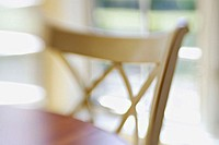 White wooden chair at wooden table, window behind in eating area, abstract view with selective focus and blur