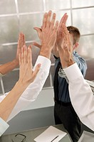 Business people giving a group high five.