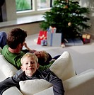 Man and two sons (7-10) playing on sofa (focus on boy in foreground)