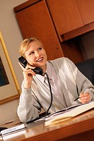 Woman in office speaking on telephone