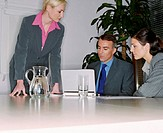 Three businesspeople looking at laptop screen in meeting room