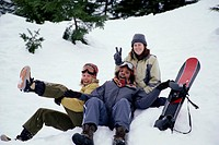 Friends sitting in snow with snowboard