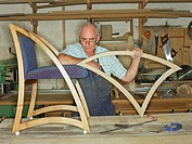 Furniture maker resting elbow on chair, portrait