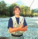 Young fly fisherman standing by river, portrait