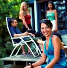 Group of friends hanging out on patio (focus on woman smiling)