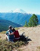 Man and woman resting on peak facing Mount Rainer, rear view