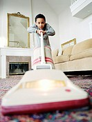 Boy (6-8) vacuuming carpet in living room, low angle view