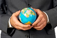 Mid section view of a businessman holding a globe