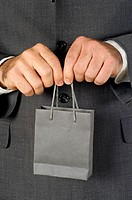 Mid section view of a businessman holding a shopping bag
